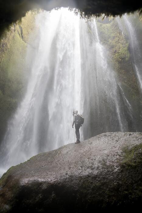 Persona bajo el agua de la cascada Gljufrabui